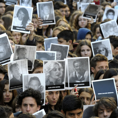 Hundreds of people hold portraits of victims of the terrorist bombing attack against the Argentine Israelite Mutual Association (AMIA) institute that killed 85 people and injured 300 during the commemoration of its 21st anniversary, in Buenos Aires on July 17, 2015. AFP PHOTO/ALEJANDRO PAGNI
